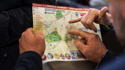 close up shot of people pointing to a sight seeing map