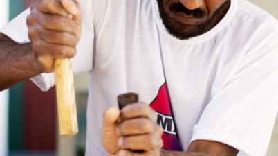 A man sculpting a wood piece carefully