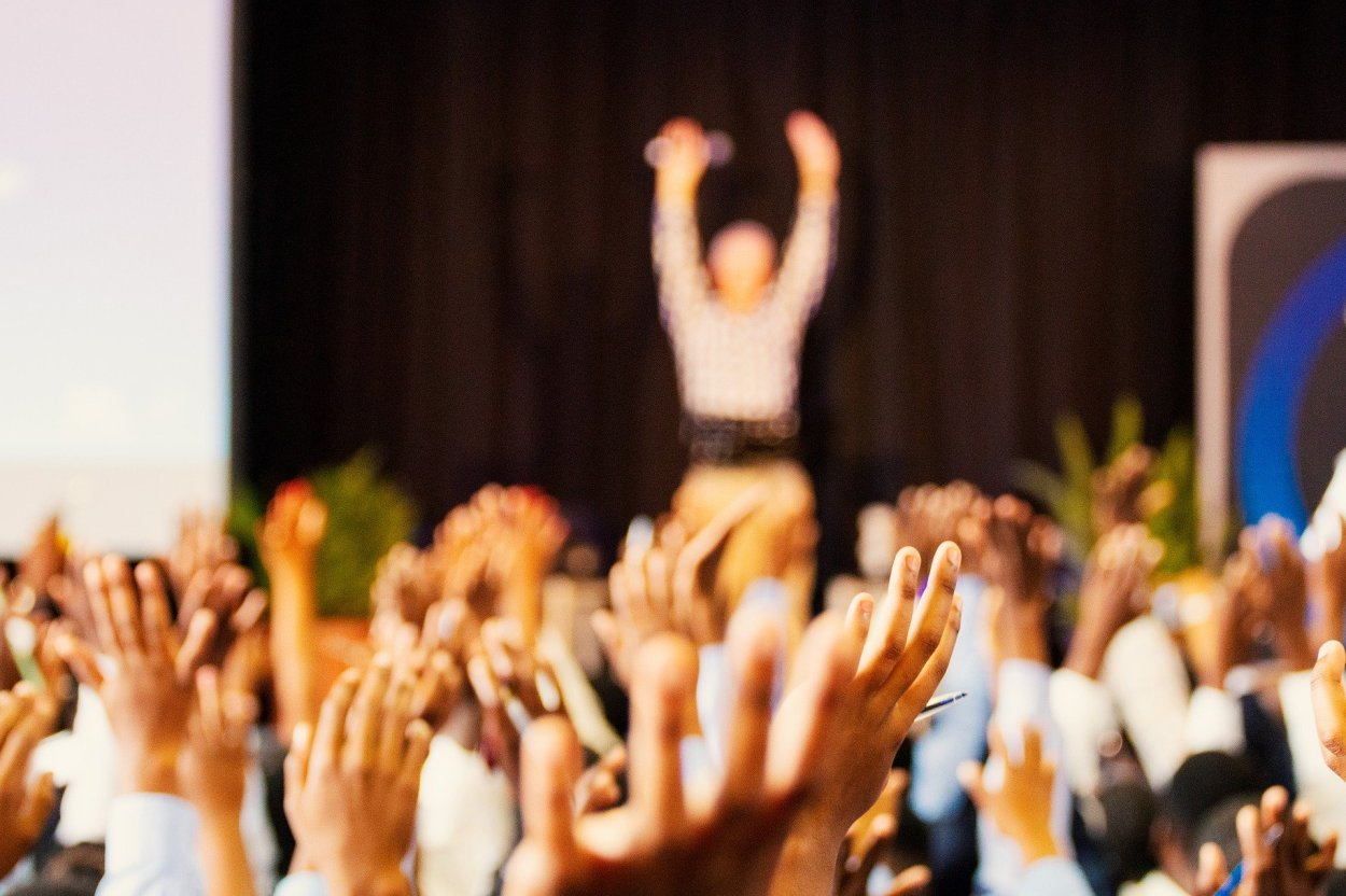 people raising their hands in a quiz competition